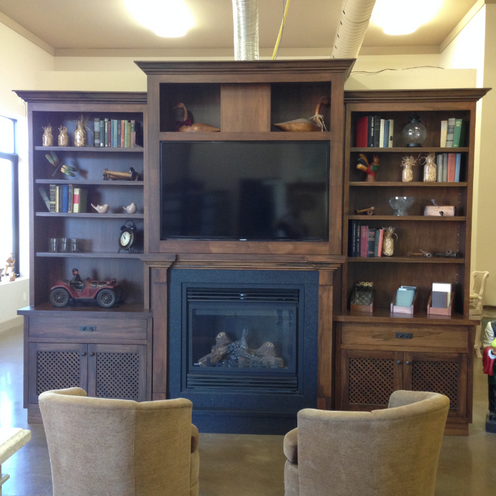Dark wood media unit including fireplace